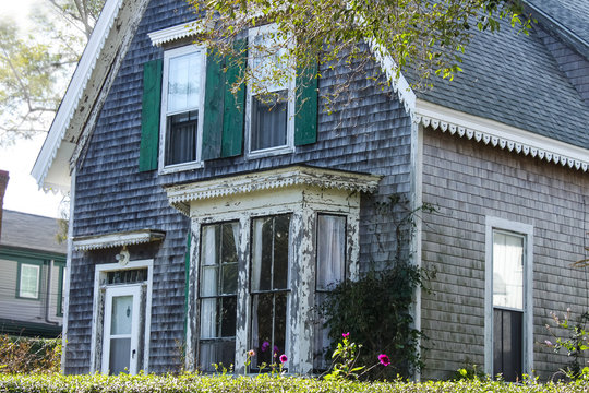 Weathered clapboard Cape Cod house with bay window and green shutters
