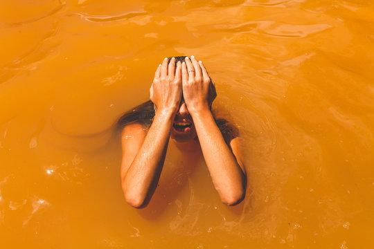 Woman swimming in resort mud pool
