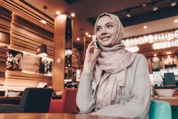 smiling beautiful Arab girl in hijab sits in restaurant, waiting for her food and talking on the phone