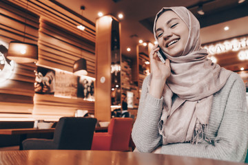a laughing young Arab girl with a headscarf on her head talking on the phone in a beautiful cozy restaurant