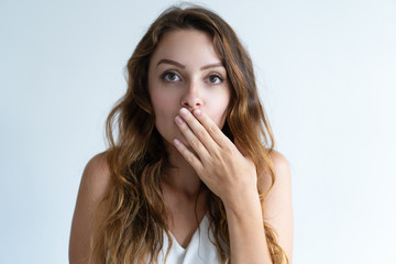 Embarrassed pretty young woman covering mouth with hand. Lady looking at camera. Embarrassment concept. Isolated front view on white background.