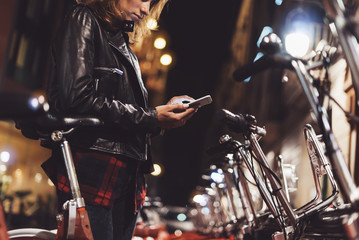 Fotomurales - girl in leather jacket using in hands screen smartphone on background bokeh light in night city street, hipster biking and riding to job by ecology  bicycle, lifestyle online wifi internet concept