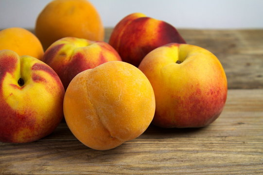 A group of ripe peaches on wooden surface