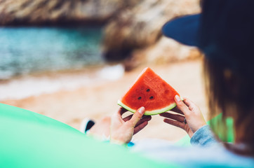 young girl hipster relax on beach coast and holds in her hand a slice of red fresh fruit watermelon on blue sea background, woman on seaside nature eating sweet healthy food