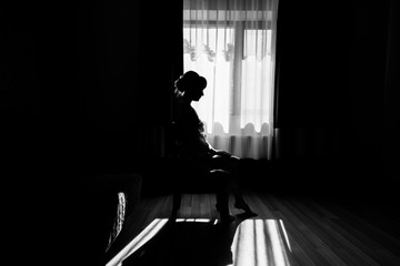 Silhouette of beautiful bride sitting on chair at the window in bedroom. Morning of the bride. Bride in gown posing in sunlight at window in morning. Getting ready. Black and white photo