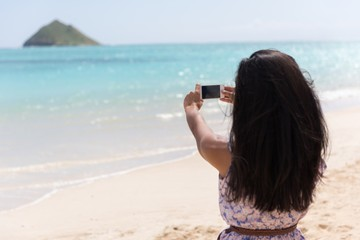 Woman clicking photo with mobile phone in the beach