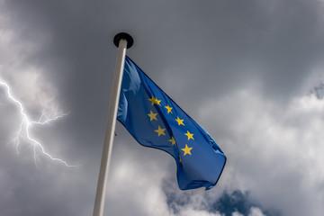 Contre-plongée du drapeau de l'Europe en pleine orage avec un éclair