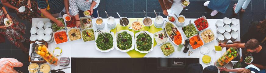 Großes vegetarisches Catering Salat  Buffet mit gesundem Essen, Salten und Obs wo sich Menschen bedienen