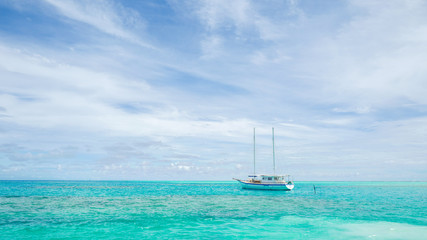 Summer concept , Boat sailing on turquoise sea color at maldives on the weekend holidays