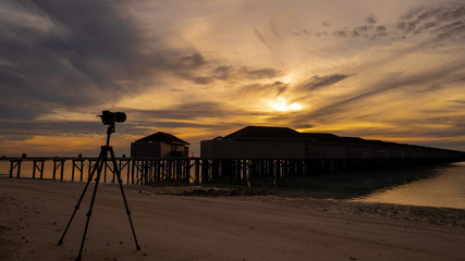 Summer concept , Camera on the beach white sand and turquoise sea color at maldives on the sunrise in weekend holidays