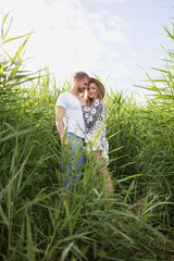 young beautiful couple of tourists walking through tall grass