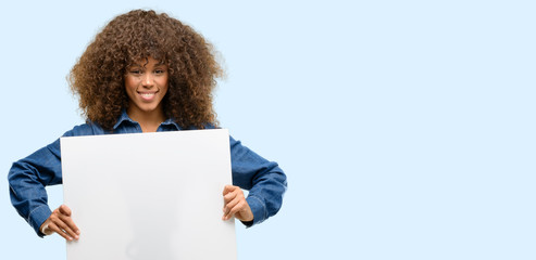 African american woman wearing blue jumpsuit holding blank advertising banner, good poster for ad, offer or announcement, big paper billboard