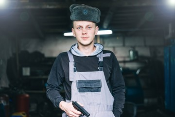 criminal man stands with a gun in the workshop in work clothes. the concept of crime in the industry.