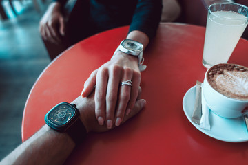 Close-up photo of female and male hands with fashion watches on red table
