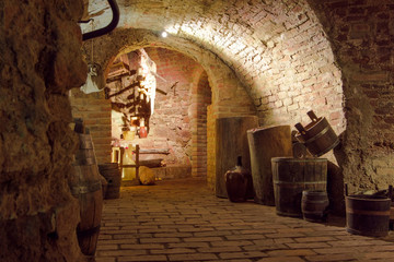 Vintage wine cellar interiors: stack of oak barrels, wooden old-style furniture with glass instruments and rack with dust covered wine bottles
