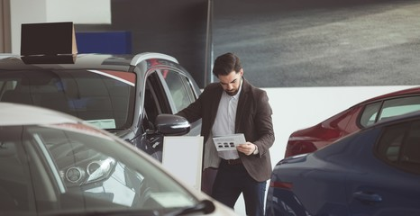 Salesman standing next to car and reading brochure
