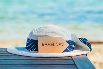 Concept of a beach holiday, white summer female hat and on wooden table on sea background and board with question travel. Vacation, holidays yes or no topic