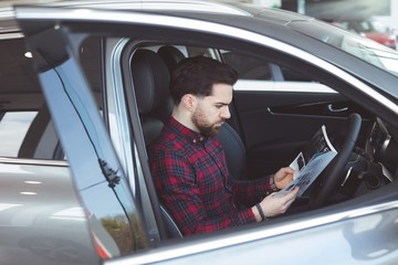 Salesman reading brochure inside the car