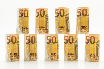 Rolled up 50 euro banknotes in rows. Isolated on a white background.