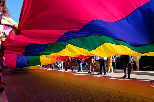 giant rainbow flag in a Pride Parade