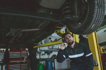 Male mechanic examining a car with torch