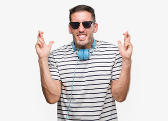 Handsome young man wearing headphones smiling crossing fingers with hope and eyes closed. Luck and superstitious concept.