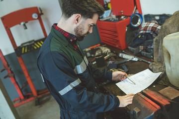 Mechanic reading instruction manual in garage