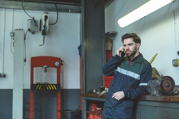 Mechanic talking on cell phone while standing in garage