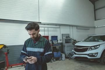 Mechanic using mobile phone while repairing car