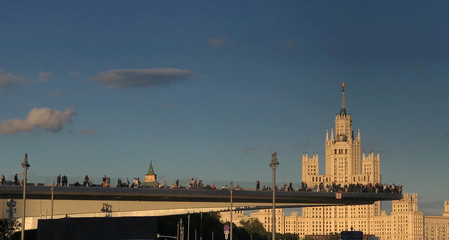 People stand on a bridge as Moscow State University building is seen in the background, in Moscow