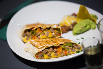 Tex-mex burrito with meat in sause on plate