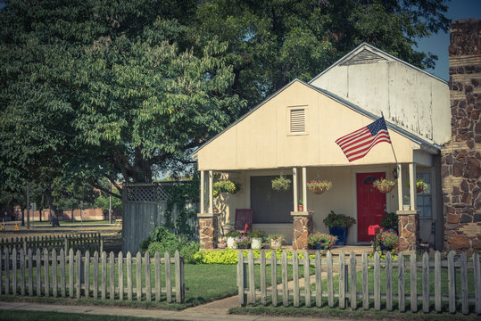 Vintage modest house with chimney in historic downtown district of Irving, Texas, USA. Classic wooden fence with well-groomed landscape, haning flower pots, big tree and proudly American flag waving