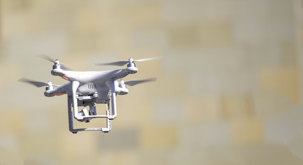 Flying Quadcopter Drone on yellow brown blurred background. Free copy text space.
