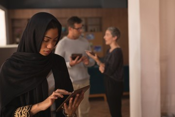 Businesswoman in hijab using digital tablet at cafeteria