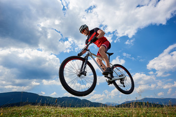 Athletic sportsman cyclist in professional sportswear and helmet flying in air on his bicycle on summer blue sky with white clouds and distant mountains on background. Outdoor extreme sport concept