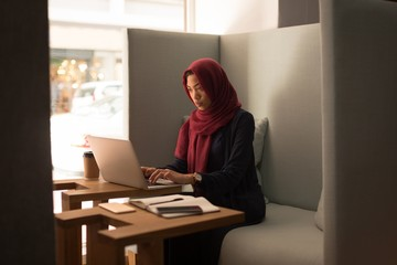 Businesswoman in hijab using laptop at cafeteria
