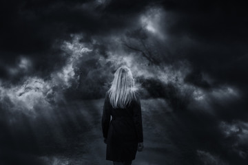 Dramatic dark stormy sky with woman walking. Double exposure effect used. Wall mural