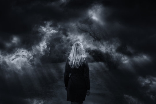 Dramatic dark stormy sky with woman walking. Double exposure effect used.