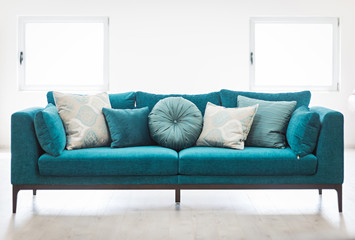 Bright living room interior with blue sofa and cushions