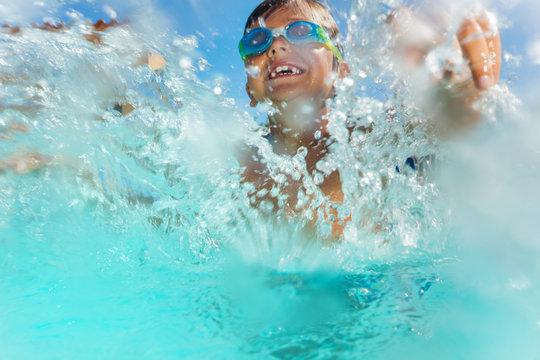 Happy boy having fun splashing water in the pool