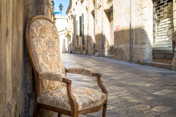 Fototapete - Old chair in a traditional street of Lecce, Italy.