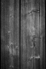 Close-up of an old and unpainted rustic wood board texture background in black and white with vignette