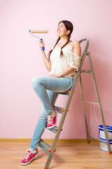 Photo of young woman with paint roller standing near staircase