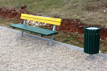 Wooden public yellow and green bench with same style trash can mounted with metal stands on playground sand surrounded with dry winter uncut grass