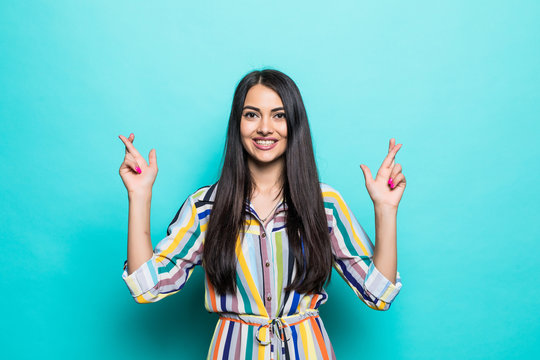 Smiling beautiful young woman with ponytail pointing up at copy space. Waist up studio shot on teal background.