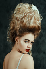 Beautiful blondie girl is sexually posing with  a Middle Ages historical hairstyle