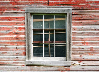 Window frame with crates in the wall  of an old wooden house.