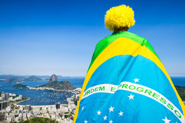 Brazilian football fan wrapped in giant flag and yellow wig  in front of Sugarloaf Mountain city skyline Rio de Janeiro.