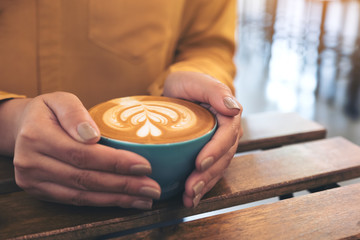 Closeup image of woman's hands holding a blue cup of hot latte coffee with latte art on wooden vintage table