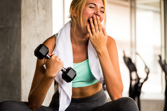 Attractive young woman exercising building muscles at the gym
